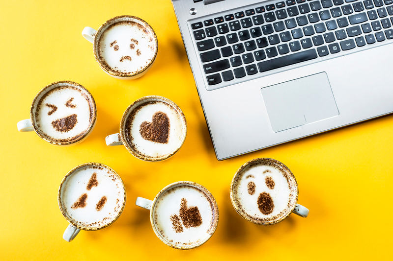 Image of laptop and various lattes with emoji faces on them. Lattes with emoji faces in a yellow background.